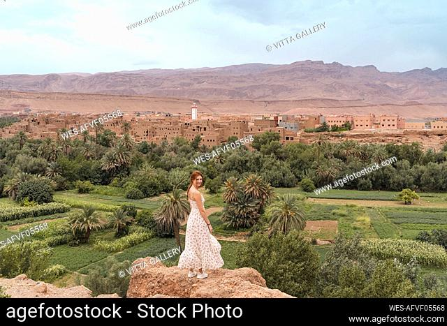 Smiling young woman standing on a rock, Ouarzazate, Morocco