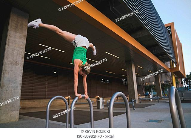 Young woman doing handstand on metal bar in urban environment