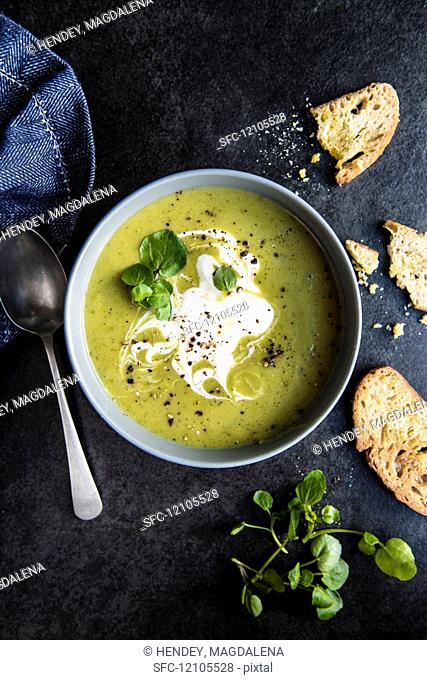 A bowl of pea and watercress soup with sour cream and bread