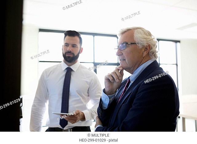 Businessmen with digital tablet planning in conference room