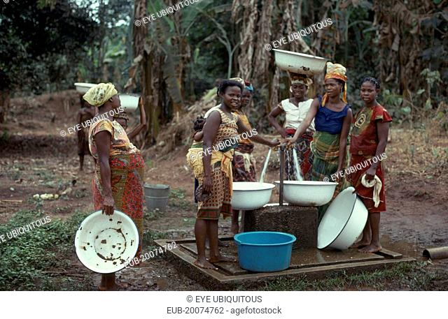 Women collecting water from well standpipe