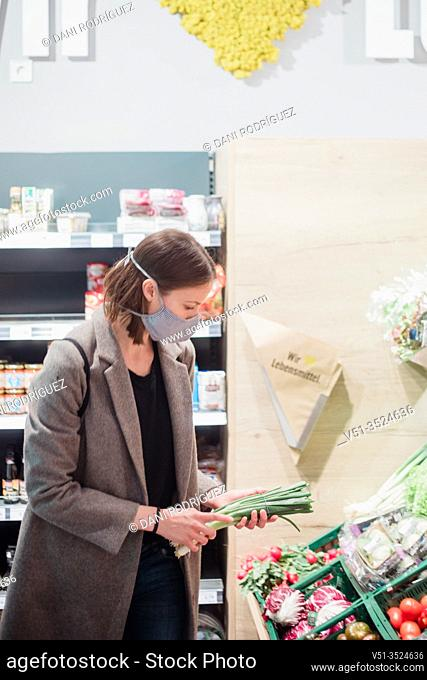 Woman in mask buying vegetables at grocery store