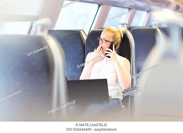 Businesswoman traveling by train, yawning while talking on cellphone and working on laptop. Long and tiresome business travel concept