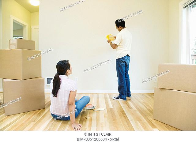 Asian couple looking at paint swatches in new house