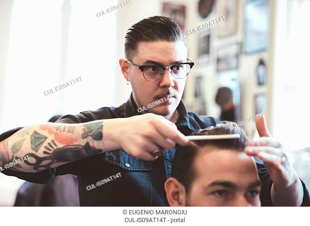 Barber combing back clients hair in barber shop