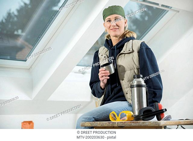 Craftswoman having a break at construction site of new building