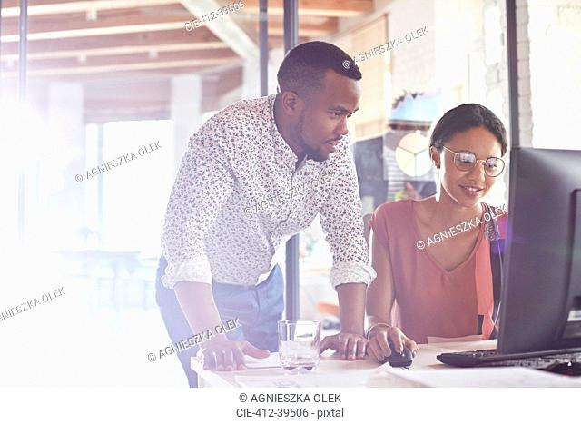 Businessman and businesswoman working at computer in office