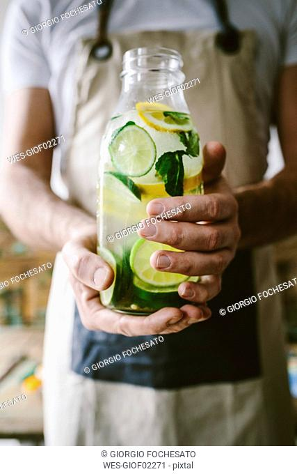 Man's hands holding glass bottle of infused water with lemon, lime, mint leaves and ice cubes