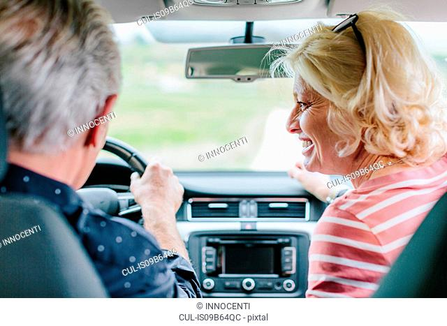 Rear view of happy tourist couple driving car