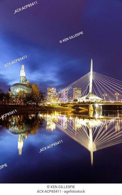 Skyline of Winnipeg at night with Canadian Museum for Human Rights and Esplanade Riel Bridge reflected in the Red River, Winnipeg, Manitoba, Canada