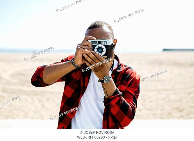 Man taking pictures with an old-fashioned camera near the beach