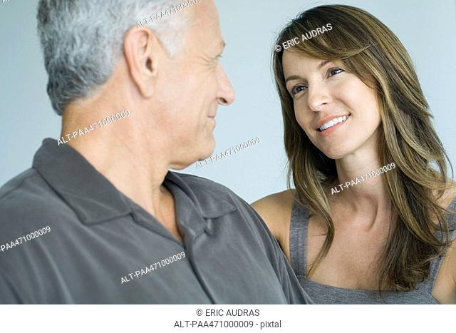 Mature man smiling at adult daughter, close-up