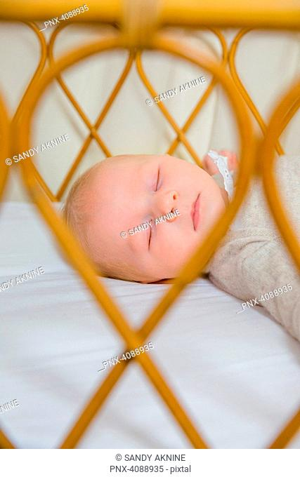 Face of a 2-month-old baby sleeping on his back, seen through the bars of his bed