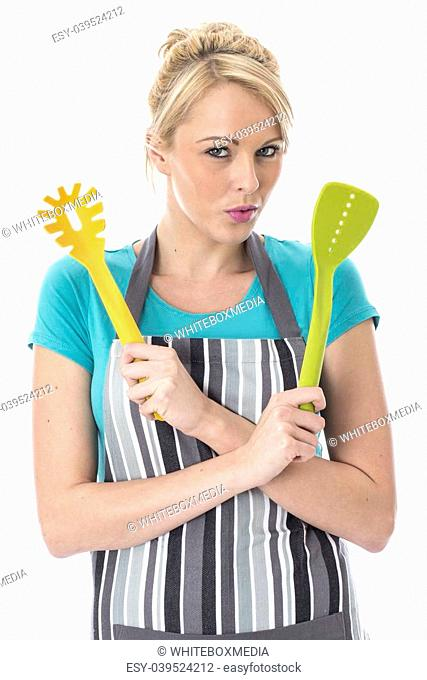 Model Released. Attractive Young Woman Holding Kitchen Utensiles