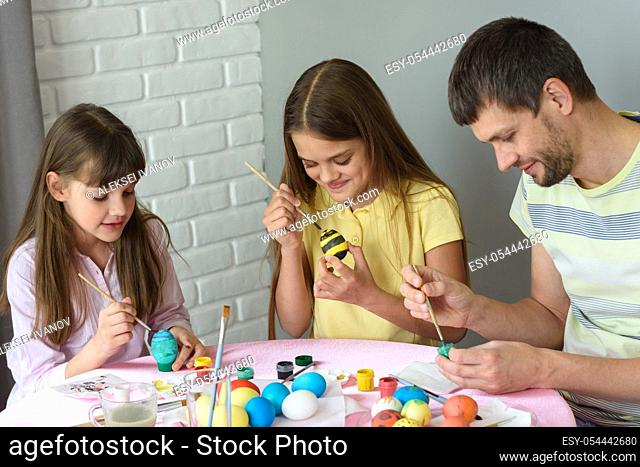 Dad with two daughters paint eggs for Easter holiday