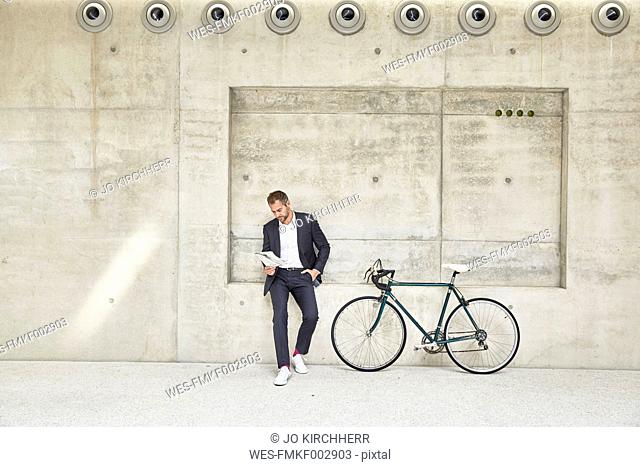 Businesssman with bicycle at concrete wall reading document