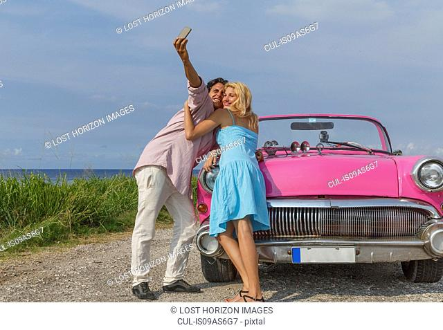 Young couple posing for selfie with vintage convertible, Havana, Cuba