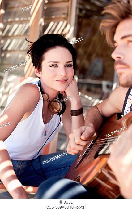 Young woman watching her boyfriend playing guitar