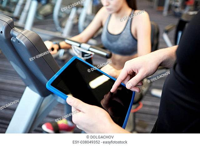 sport, fitness, lifestyle, technology and people concept - close up of trainer hands with tablet pc computer and woman working out on exercise bike in gym