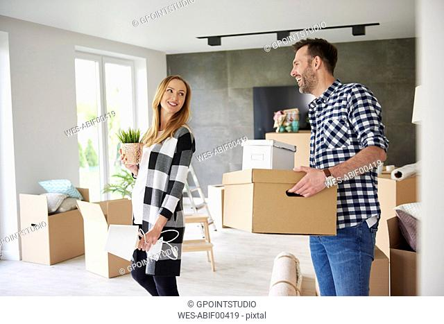 Happy couple moving house carrying cardboard box and plant