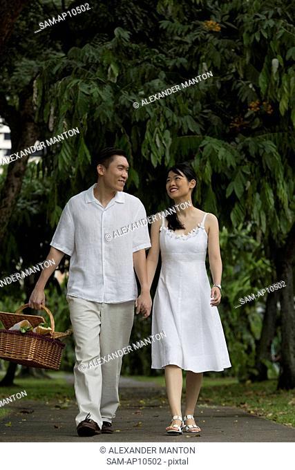 Singapore, Man and woman walking through park