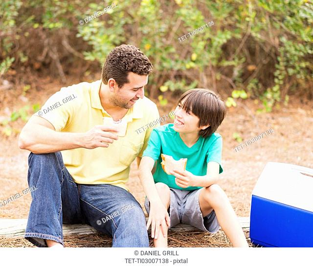 Father and son (12-13) eating sandwiches in forest