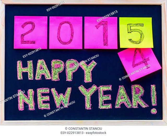 Happy New Year 2015 message hand written on blackboard, numbers stated on post-it notes, 2015 replacing 2014, corporate office celebration concept