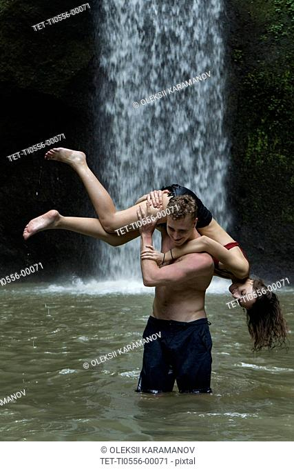 Young man carrying young woman over his shoulder in river by Tibumana Waterfall in Bali, Indonesia