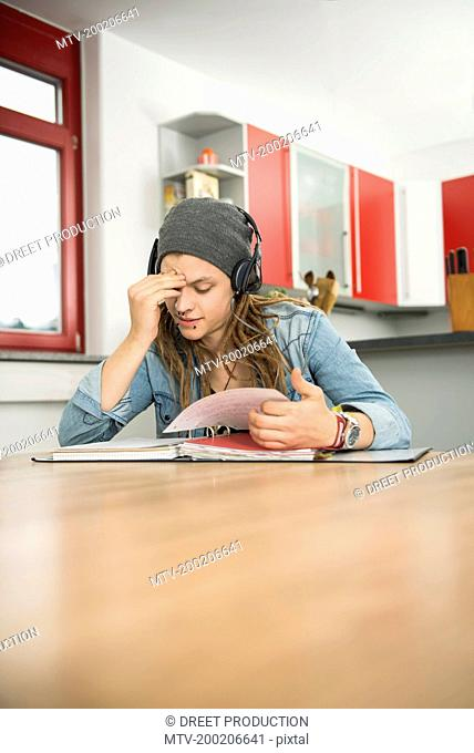 Young man wearing headphones and studying at home, Munich, Bavaria, Germany