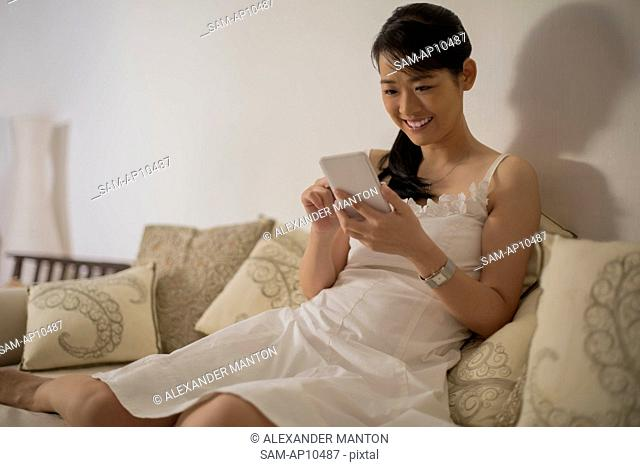 Singapore, Woman sitting on sofa using smart phone