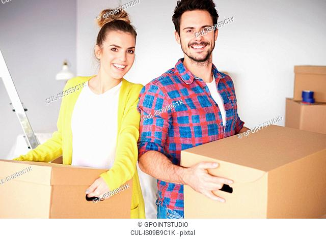Young couple moving home, holding cardboard boxes, smiling
