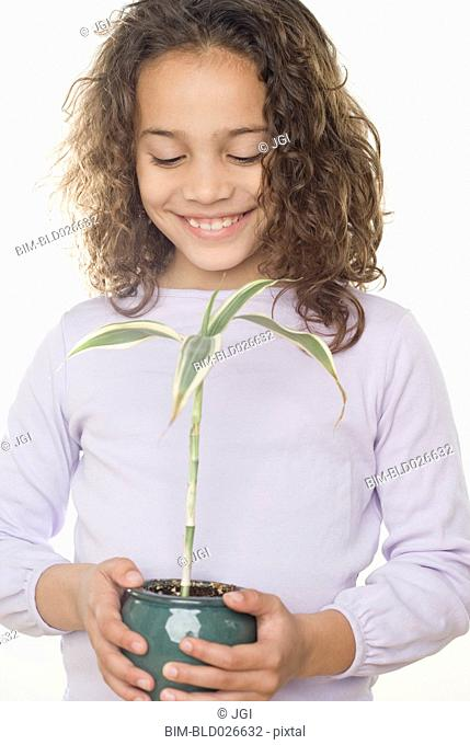 Young girl holding potted plant