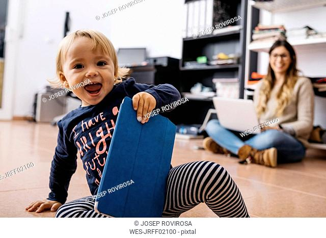 Happy little girl sitting on the floor at home with tablet and mother in background