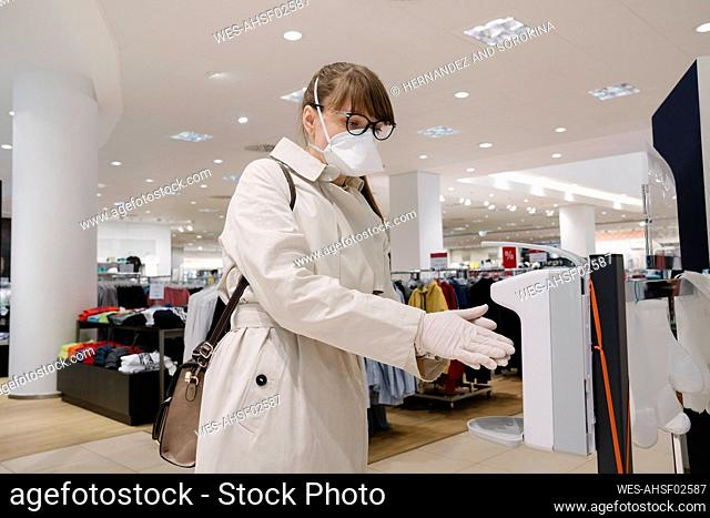 Woman with face mask and disposable gloves disinfecting her hands before shopping in a fashion store