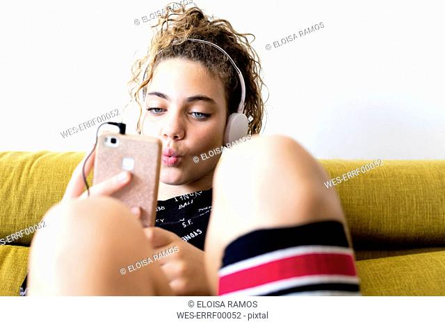 Portrait of whistling girl sitting on the couch listening music with headphones and smartphone