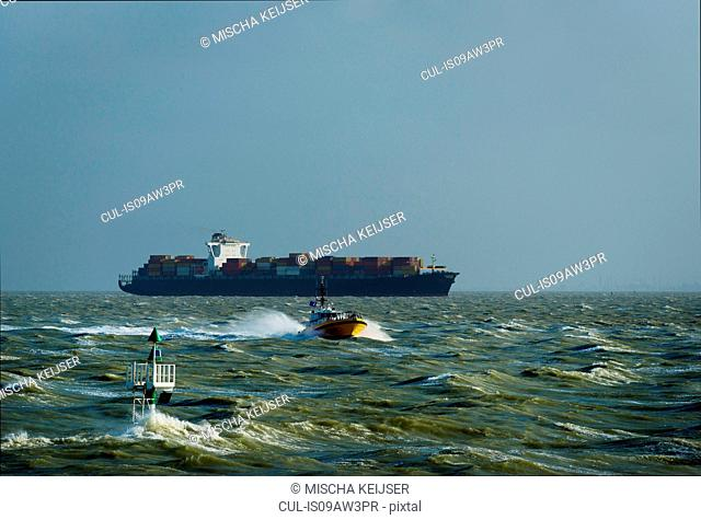 Container ship sailing on the Westerschelde river, towards open sea, after visiting Antwerp harbour. The pilot has been collected from the ship by the pilots...