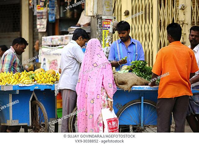 Bangalore, India - October 23, 2016: Unknown married Indian couple buying green leaf vegetables from a street side seller in the Avenue road