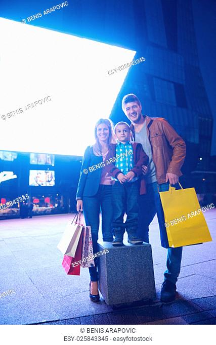 Group Of Friends Enjoying Shopping Trip Together.group of happy young frineds enjoying shopping night and walking on steet on night in with mall in background