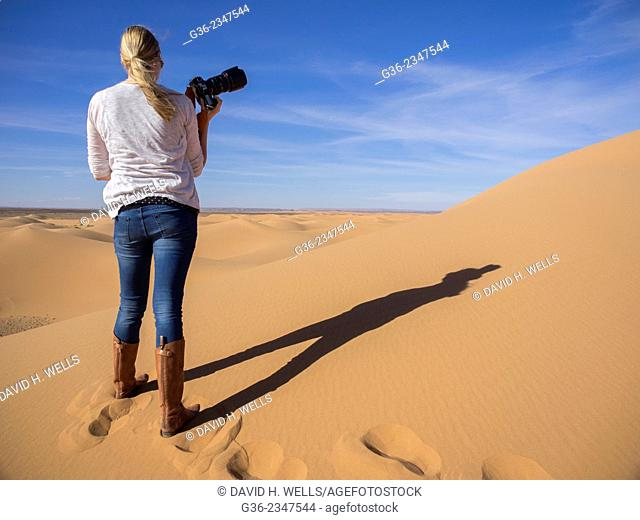 Rear view of woman with slr camera on desert at Morocco
