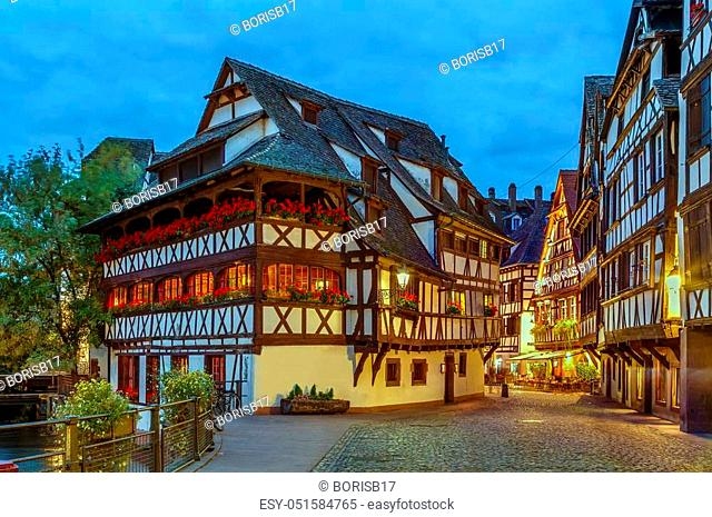 Street with historical half-timbered houses in Petite France district with Maison des Tanneurs (tanners house), Strasbourg, France. Evening