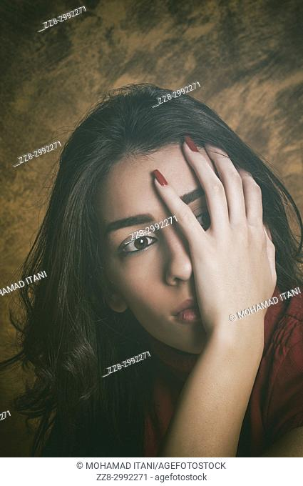 Scaered young woman hand covering face looking away
