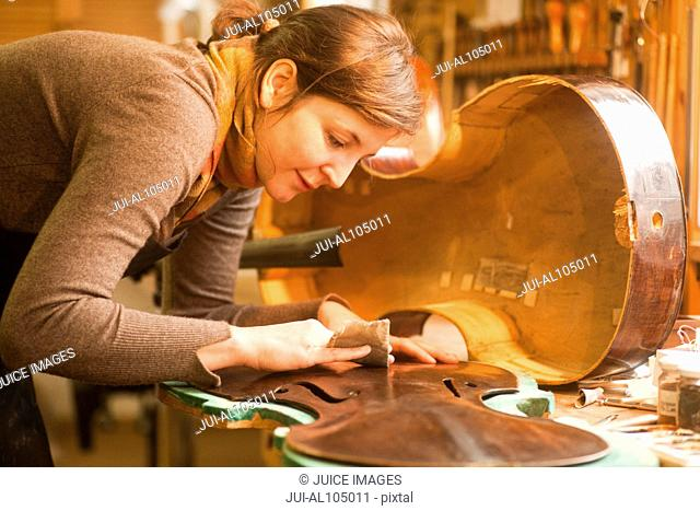 Violin maker repairing a cello in workshop