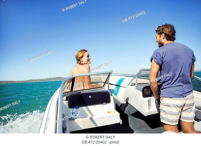 Man steering boat with girlfriend