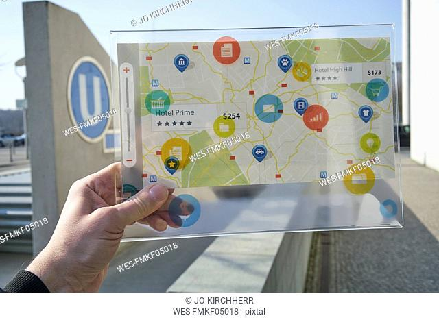 Hand holding futuristic device with digital icons and map in the city
