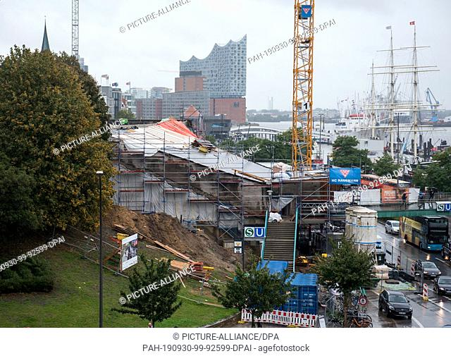 29 September 2019, Hamburg: View of the construction site at the subway station Landungsbrücken at the harbour. The Elbphilharmonie can be seen in the...