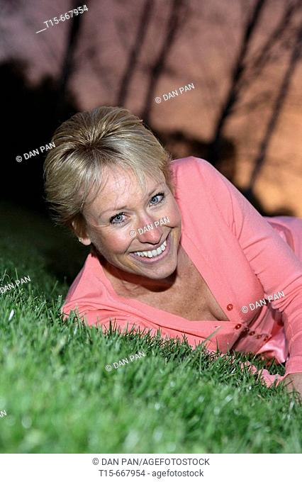Middle aged blond woman dressed up playfully on the grass to enjoy the sunset or sunrise