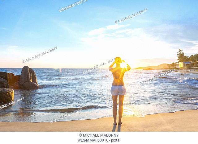 Woman on the beach taking pictures with her smart phone