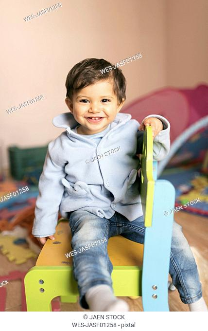 Portrait of smiling baby boy sitting on chair