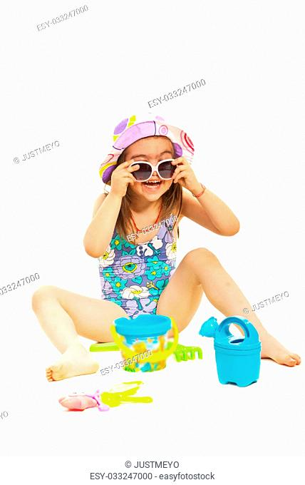 Little girl in swimsuit with sunglasses having fun isolated on white background