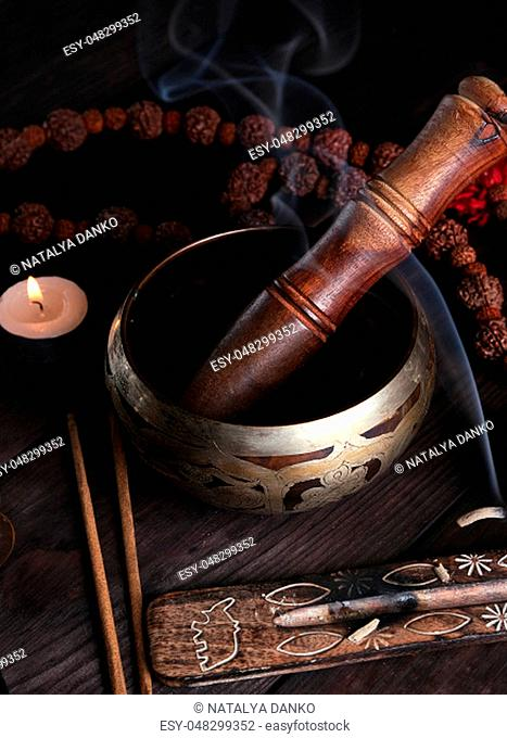 copper singing bowl and a wooden stick on a brown table, a stick with incense is burning nearby